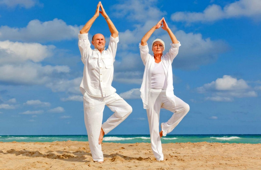 an-old-couple-doing-yoga-on-the-beach